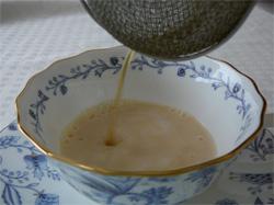 牛乳に紅茶を注いでいる写真