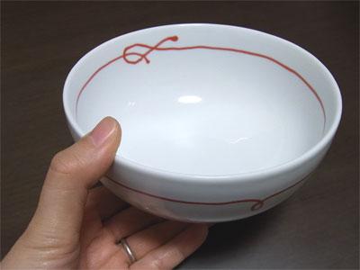 白山陶器の赤い糸 ペア小丼を片手にもったところ