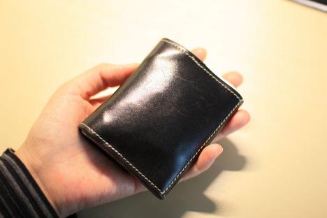紺色の栃木レザーの革財布を左手でもっているところ